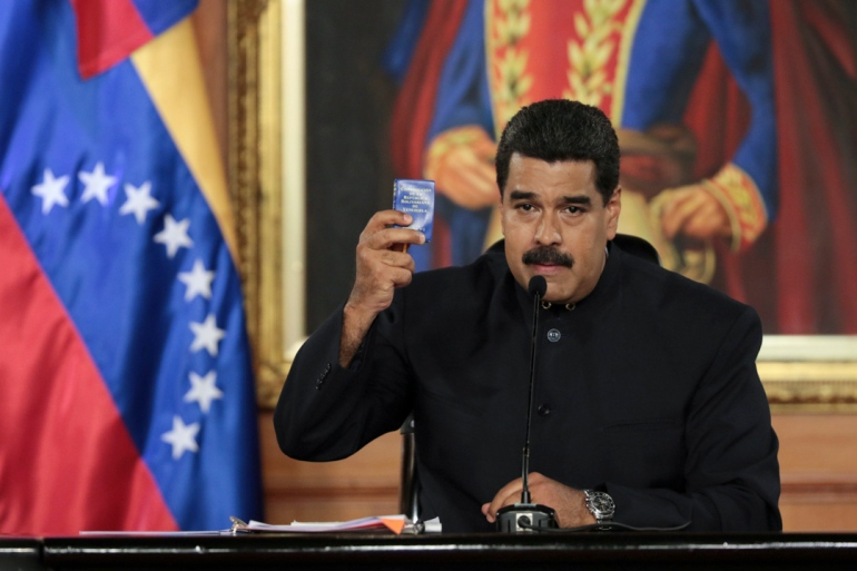 Venezuela's President Nicolas Maduro holds a copy of the Venezuelan constitution as he speaks during a ceremony at Miraflores Palace in Caracas