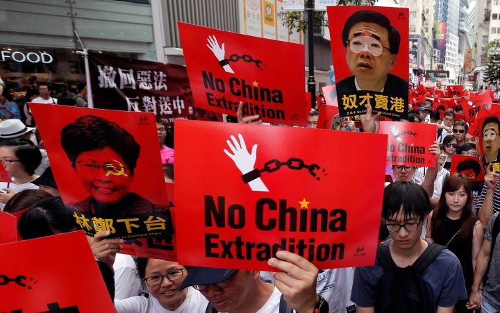 Demonstrators hold signs during a protest to demand authorities scrap a proposed extradition bill with China, in Hong Kong
