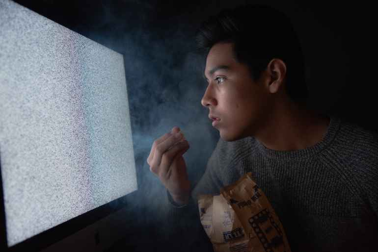 man eating chips while watching tv