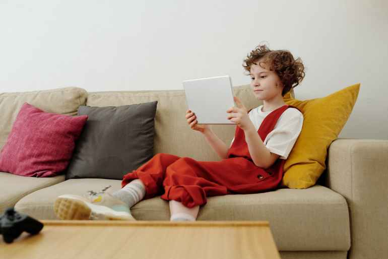photo of child sitting on couch while holding tablet